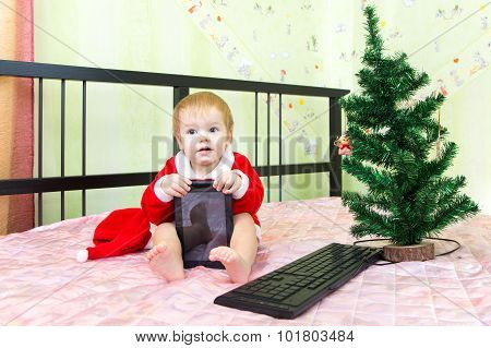 Pleased baby in new year suit with tablet computer poster
