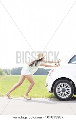 Side view of woman pushing broken down car on country road