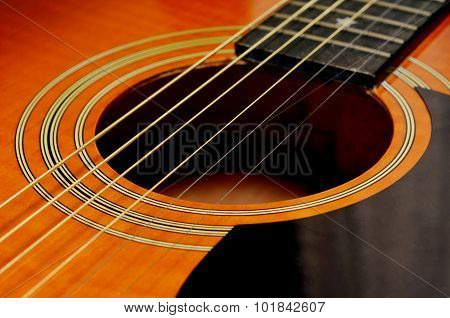 Sound-hole of six-string folk acoustic guitar. close up.