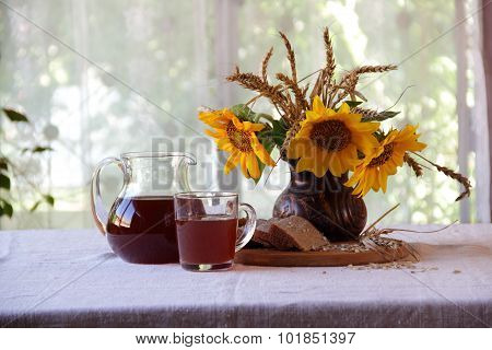 Kvass (kvas) In A Transparent Jug, Bread And A Bouquet Of Sunflowers