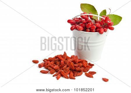 Metal Bucket With Barberries Near Heap Of Goji Berries  Isolated On White Background