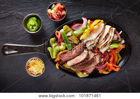 aerial view of a iron skillet filled with steak and chicken mexican fajitas on slate