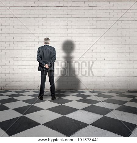 businessman with pawn shadow on a chess board
