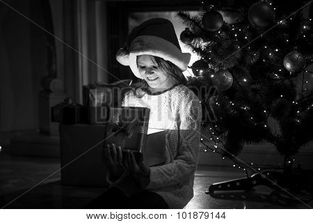 Smiling Girl Looking Inside Of Glowing Gift Box At Christmas Eve