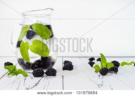 Healthy detox water with blackberry and mint. Cold refreshing berry drink with ice on white wooden t