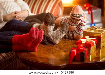 Closeup Photo Of Family's Legs In Woolen Socks Next To Fireplace