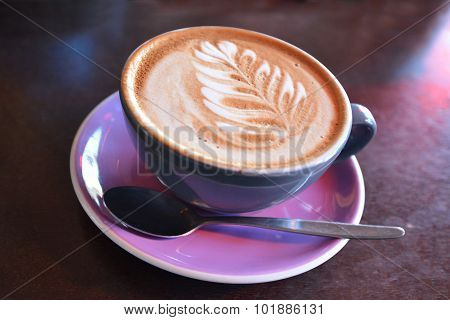 Flat white coffee decorated with the New Zealand iconic symbol the silver fern on it. Copy space