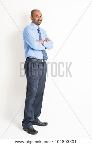 Portrait of full body mature Indian business man with blue shirt arms crossed standing on plain background.