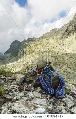 Dynamic rope helmet carabiners climbing harness and descender in the mountain valley poster