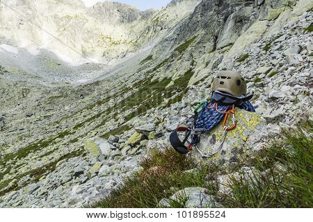 Dynamic rope helmet carabiners climbing harness and descender on a rock ridge in the background poster