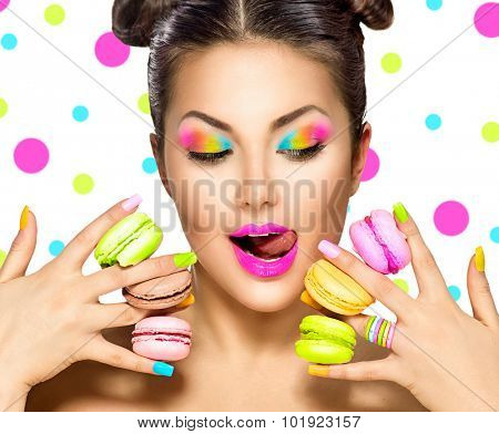 Beauty fashion model girl with colourful makeup and manicure taking colorful macaroons. Beautiful woman, bright make-up. Purple lipstick, vivid eyeshadow and accessories. Diet, dieting concept. Sweets