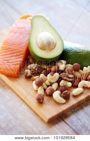 healthy eating, protein diet and culinary concept - close up of salmon fillets, avocado and nuts on table