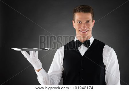 Young Waiter Holding Silver Tray In Hands poster