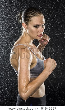 poster of Half Body Shot of a Wet Female Fighter in Combat Pose, Looking Fierce at the Camera Against Black Background with Water Drops.