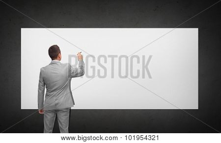 business, people, advertisement , information and office concept - businessman writing or drawing something imaginary on white board from back over dark gray background