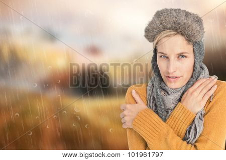 Woman in winter clothes shivering over white background against country scene