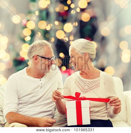 family, holidays, age and people concept - happy senior couple with gift box over christmas tree lights background