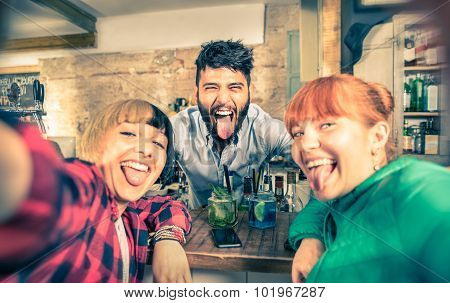 Young Handsome Bartender Flirting With Beautiful Girls At Cocktail Bar - Happy Girlfriends Selfie