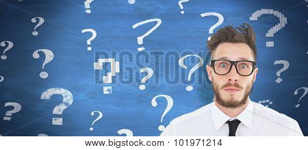 Geeky young businessman looking at camera against blue chalkboard