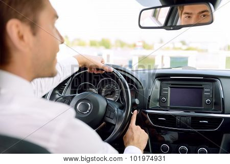 Pleasant businessman driving a car
