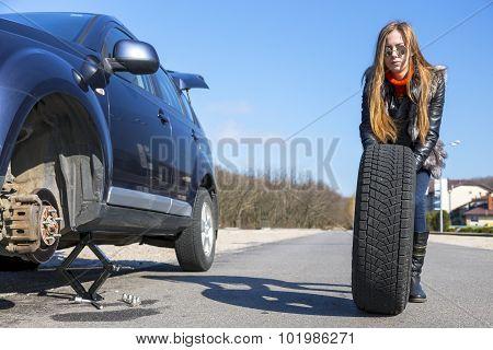 Female biker rolls big wheel