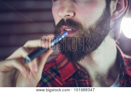 Close-up of hansome man holding electronic cigarette