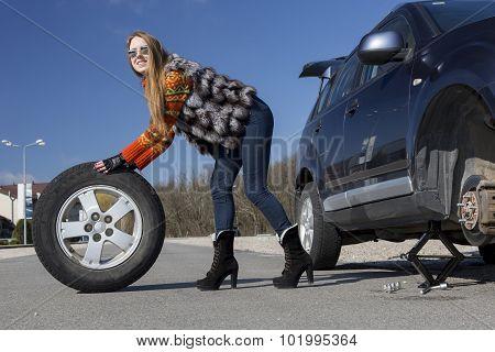 Leggy beautiful female holds big wheel