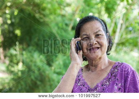 60 Years Old Thai Woman Smiling While Talking On Mobile Phone