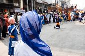 Several local Sikh people including both men and women gathering to offer prayer in front of a religious march in Delhi. On the background, the religious ceremony is seen. poster
