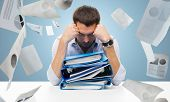 business, people, deadline, stress and paperwork concept - sad businessman with stack of folders and falling papers over blue background poster