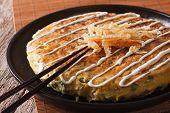 Japanese pizza: okonomiyaki on a plate close-up and chopsticks. horizontal poster