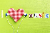 The word I love music in cut out magazine letters with earphones poster
