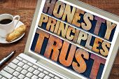 honesty, principles and trust concept - words in vintage letterpress wood type printing blocks stained by color inks on a laptop screen with a cup of coffee poster