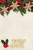Christmas background border with gold joy sign, snowflake bauble decorations, holly and winter greenery over old parchment paper. poster