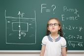 girl drawing physical phenomenon gravity on school board poster