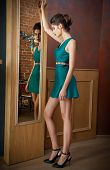Elegant young woman in turquoise short dress looking into a large mirror, side view. Beautiful slim girl with creative hairstyle posing in front of a wall mirror, indoors shot. Fashionable model. poster