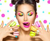 Beauty fashion model girl with colourful makeup and manicure taking colorful macaroons. Beautiful woman, bright make-up. Purple lipstick, vivid eyeshadow and accessories. Diet, dieting concept. Sweets poster