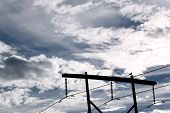 A silhouette of a bird perched on a power pole against a blue and cloudy sky. poster