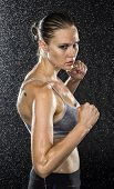 Half Body Shot of a Wet Female Fighter in Combat Pose, Looking Fierce at the Camera Against Black Background with Water Drops. poster