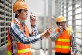 Foreman talking on walkie-talkie at the construction site poster