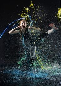 Woman High Kicking in Colorful Water Splashes