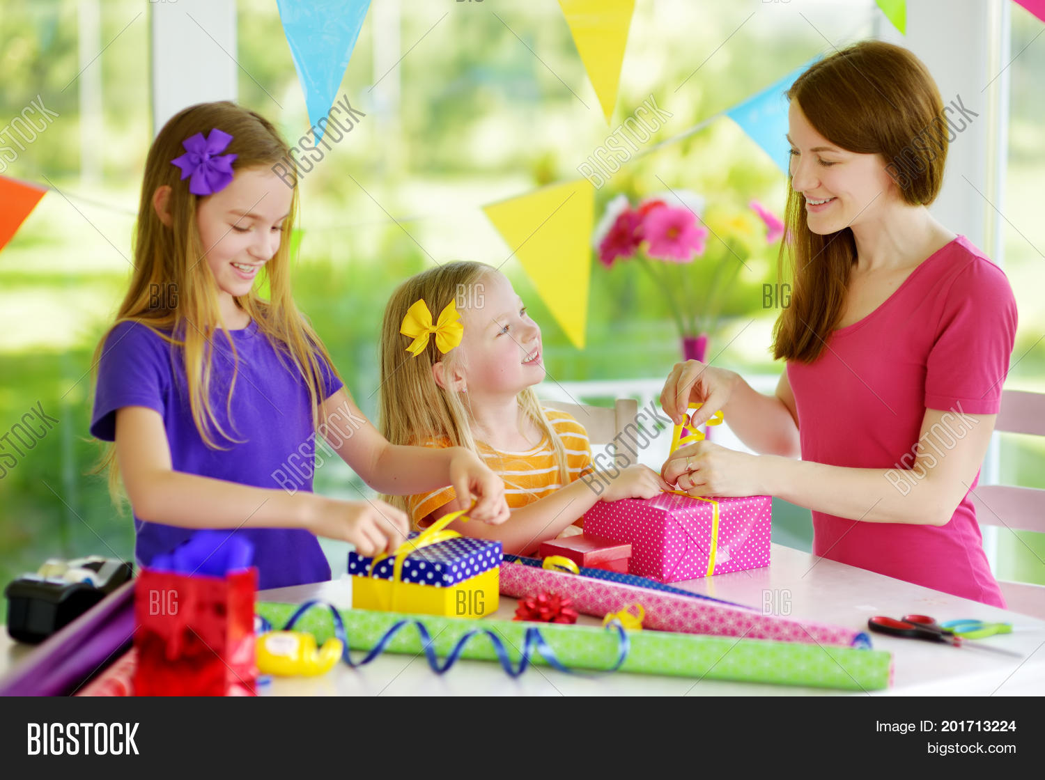 Two Cute Sisters And Their Young Mother Wrapping Gifts In Colorful Paper Family Of