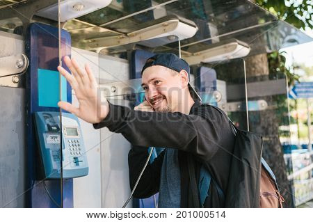 A young attractive modern man speaks at a payphone and welcomes with his hand.