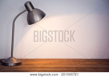 Illuminated table lamp on wooden table by wall in office