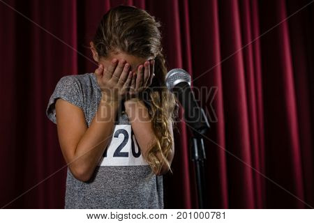 Girl covering her face with hand on stage in theatre