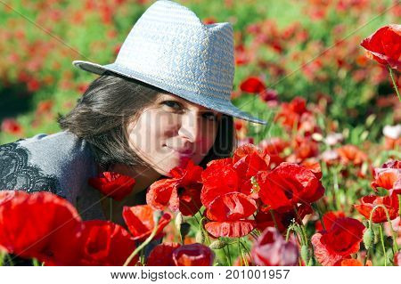 Portrait of beautiful brunette in a summer hat against a background of red poppies in the height of summer. Beautiful woman enjoying the bright red wild flowers, harmony concept.