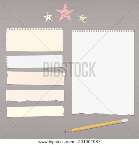 White, beige note, copybook, notebook paper strips, stars and pencil on dark grey background