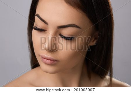 Eyelashes extensions. Fake Eyelashes. Closeup Of Beautiful Young Female Model With Soft Smooth Skin And Professional Facial Makeup. Portrait Of Sexy Girl With Long Fake Eyelashes And Perfect Make-up.