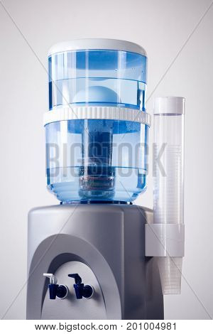 Drinking glasses on water cooler against white background