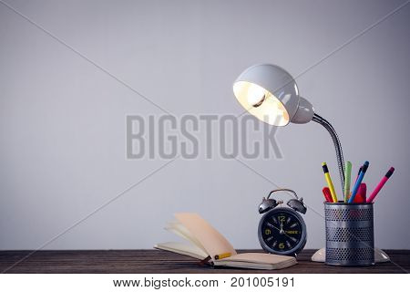 Illuminated lamp with desk organizer by book and alarm clock on table against wall